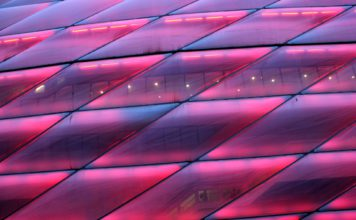 """Embellished Close-up of the """"Emperors Closet"""", stadium of Bayern München, shining in all shades alongside of the motorway."""
