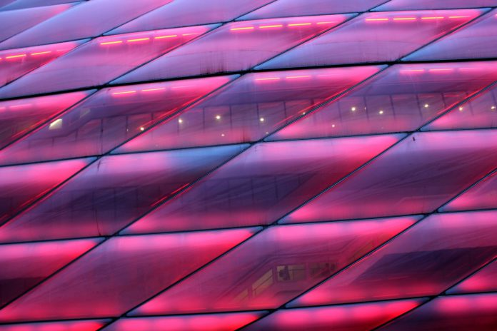 "Embellished Close-up of the ""Emperors Closet"", stadium of Bayern München, shining in all shades alongside of the motorway."
